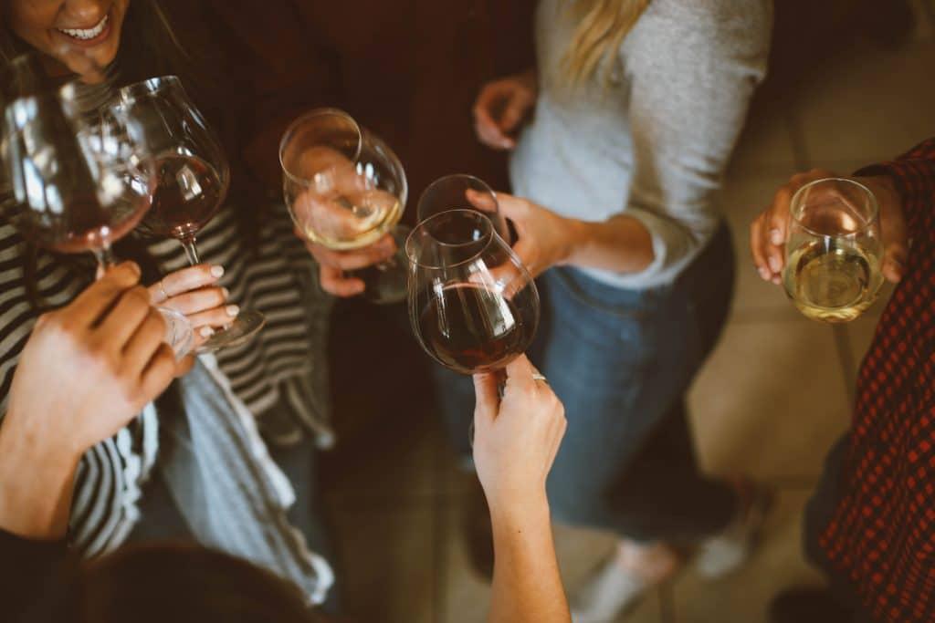 """Des amis se regroupent autour d'un verre de vin. Cette image illustre la fonction """"virements par SMS"""" de Ma French Bank."""